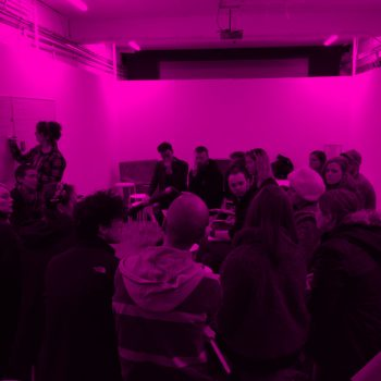 A Group of people sitting in a room with one person writing on a whiteboard, the image is over-layed with a pink filter